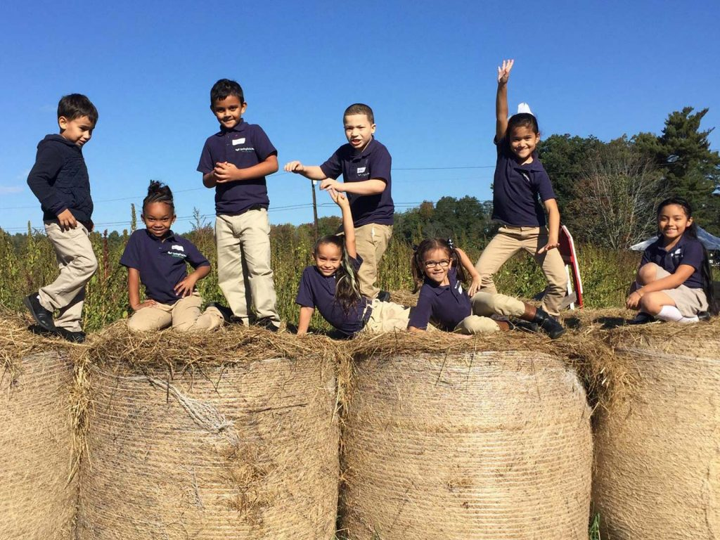 Kids from Springfield Prep play on hay bales